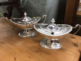 A pair of silver plate sauce tureens in the Adam style of oval form on a raised foor with gadroon bo