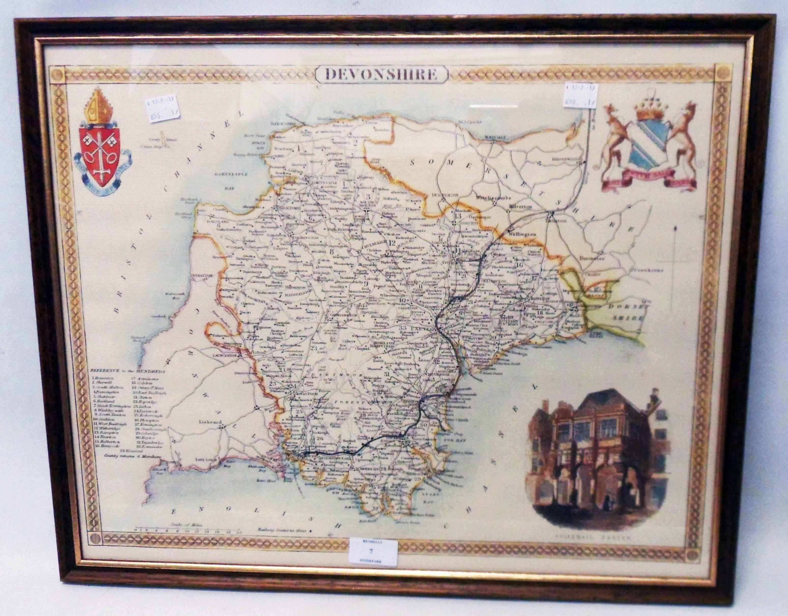 A framed reproduction coloured map print of Devonshire