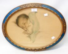 A decorative oval framed coloured print, depicting a sleeping baby