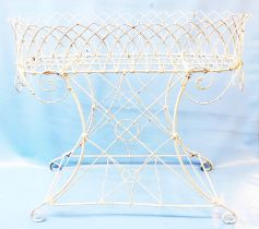 A late Regency wirework garden planter of oval form with crenulated top and scrolls, set on