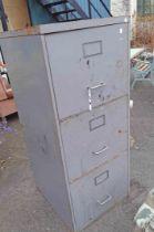 A vintage grey metal painted three drawer filing cabinet