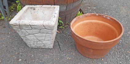 A terracotta plant pot and concrete brick form planter