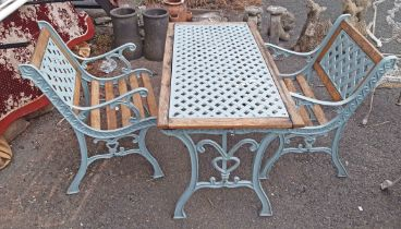 A cast iron table and two patio chairs - sold with an iron chair back