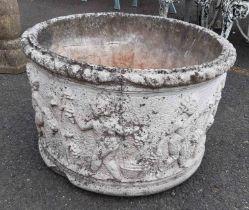 A large concrete round garden planter with classical frieze decoration