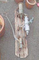 An antique farmhouse hand water pump on remains of mounting board