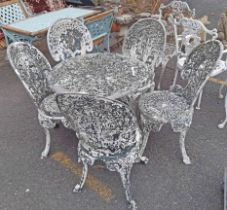 A vintage cast aluminium patio set of four chairs and table with remains of painted finish