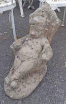 A concrete garden statue of a seated gnome