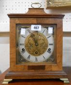A vintage walnut cased bracket clock with brass and silvered dial and eight day chiming movement