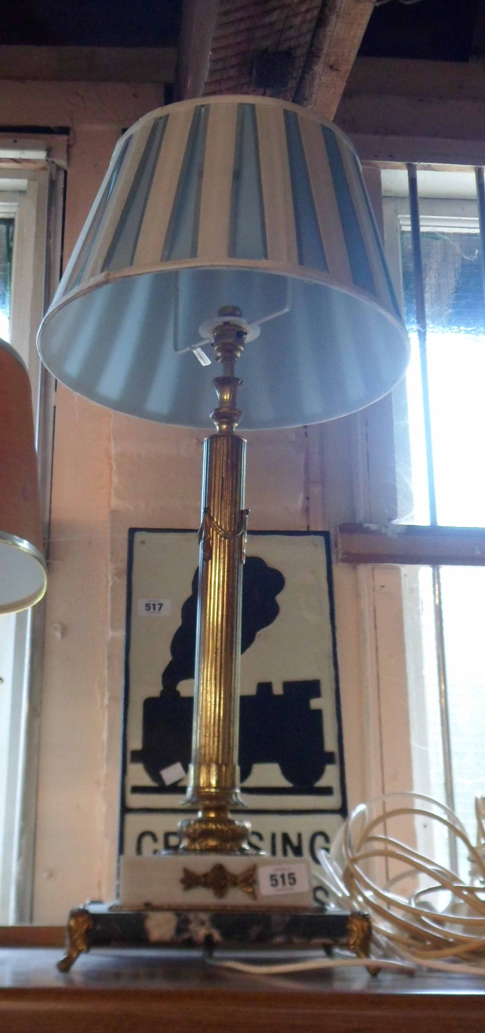 A large Corinthian column cast brass table lamp set on stepped marble and slate plinth