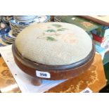 A Victorian stained wood circular footstool with tapestry upholstery, set on turned feet