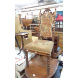 A late Victorian oak framed baronial standard chair with original upholstery and flanking barley