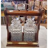 A two bottle oak tantalus with pair of cut glass spirit decanters (ground chips to decanters) - with