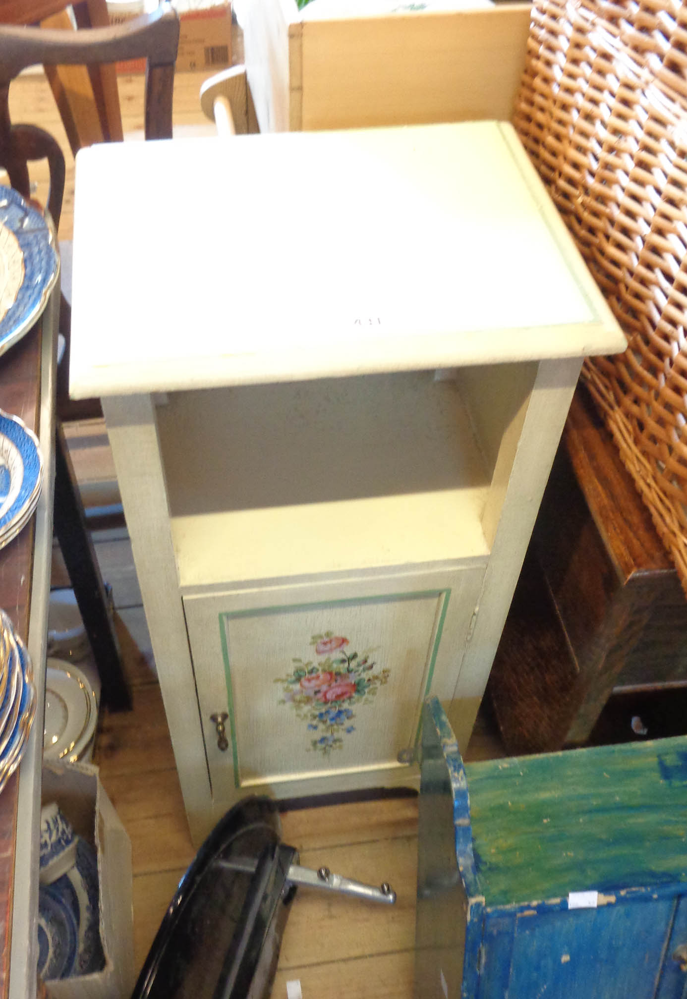 A 20th Century painted wood pot cupboard with recess and floral decorated cupboard door under