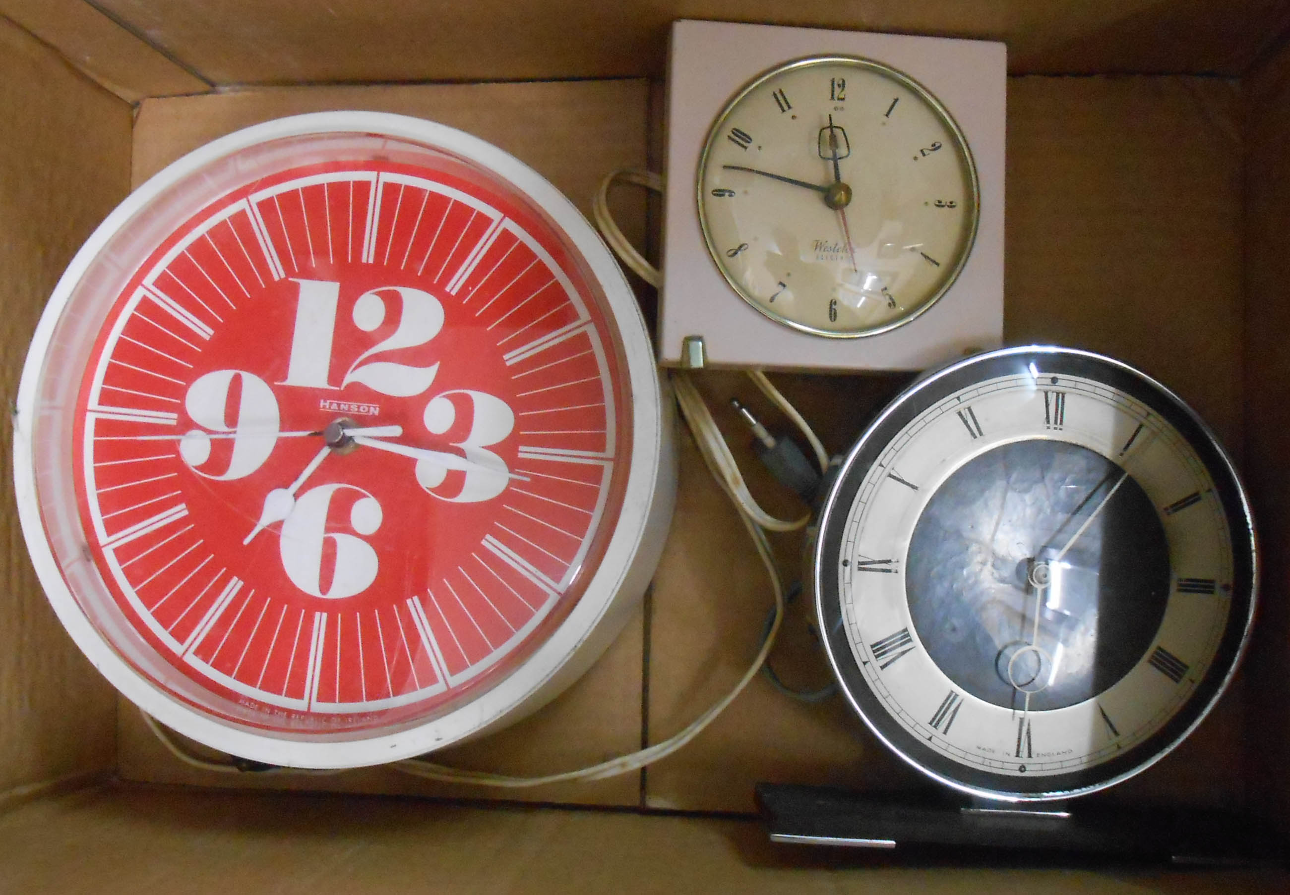 Two vintage electric timepieces and a battery wall clock