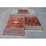 Three Middle Eastern small handmade mats each with central medallion and geometric border, flanked