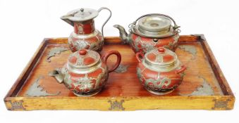 An early 20th Century Chinese pewter clad terracotta tea service comprising two teapots, hot water