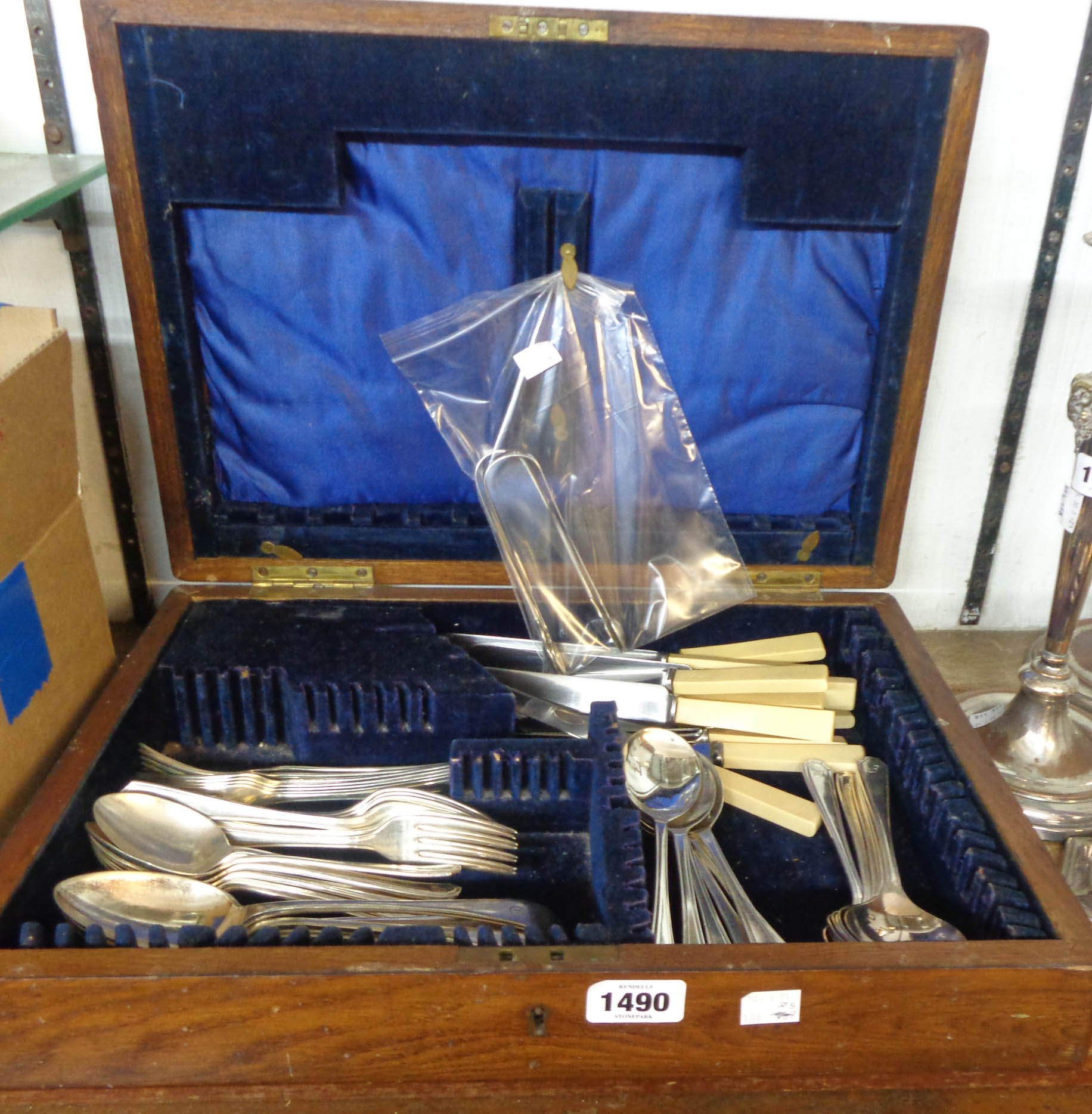 A vintage oak canteen containing assorted silver plated cutlery and two pairs of silver sugar tongs