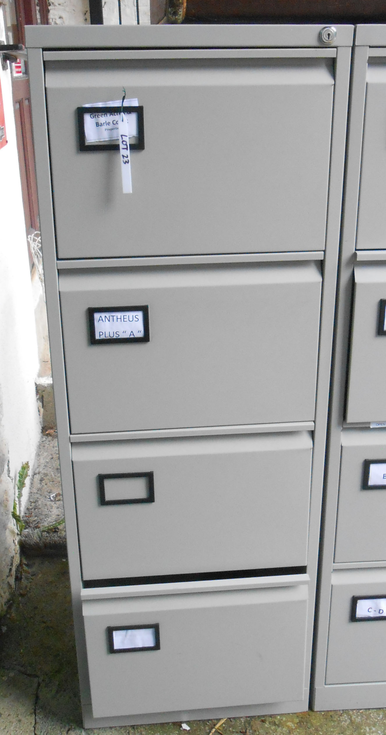 A modern four drawer grey painted filing cabinet - with key