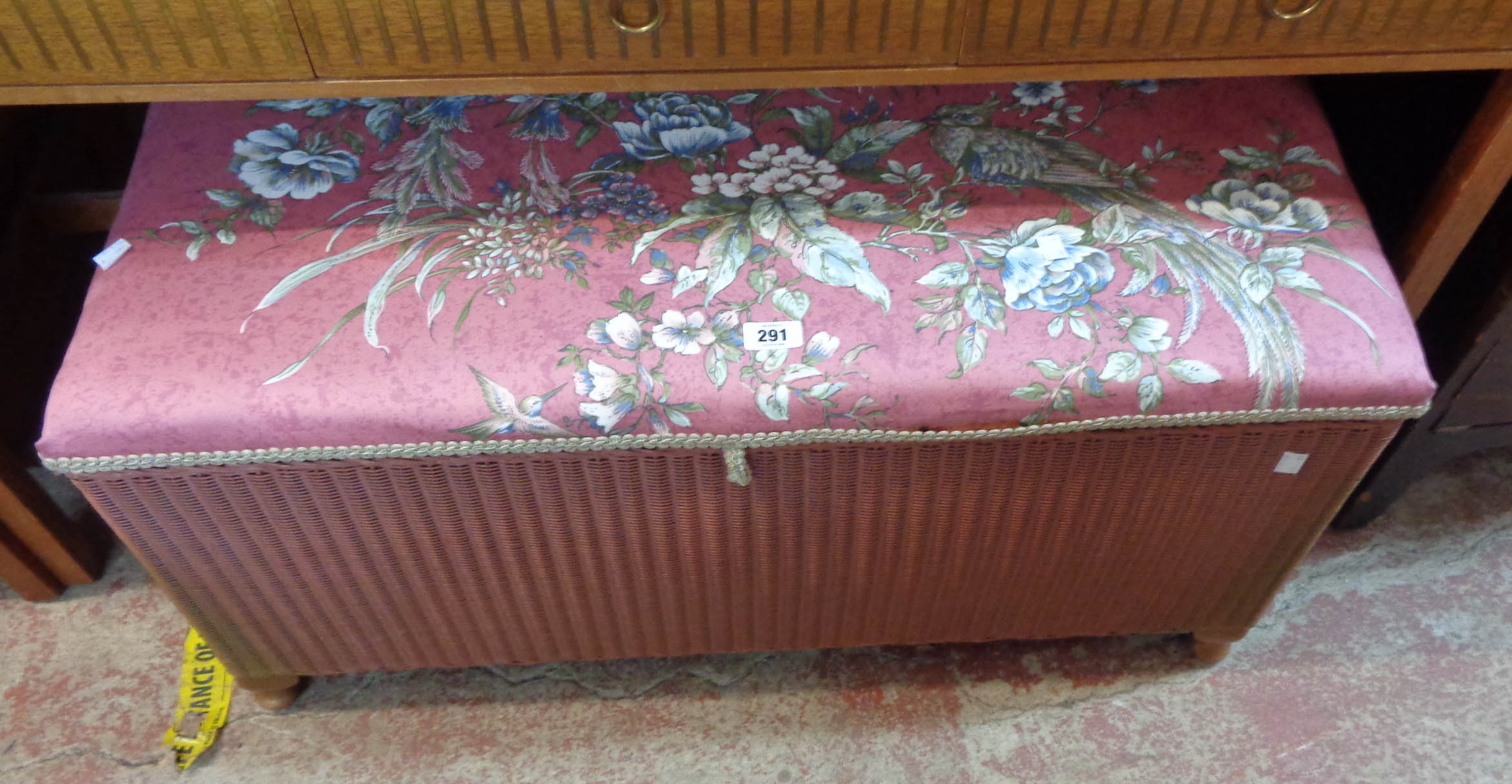A vintage Lloyd Loom ottoman with original upholstery and old rose coloured finish, set on short