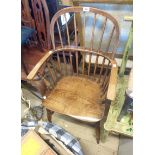An antique elm hoop stick back elbow chair with solid moulded seat, set on turned supports