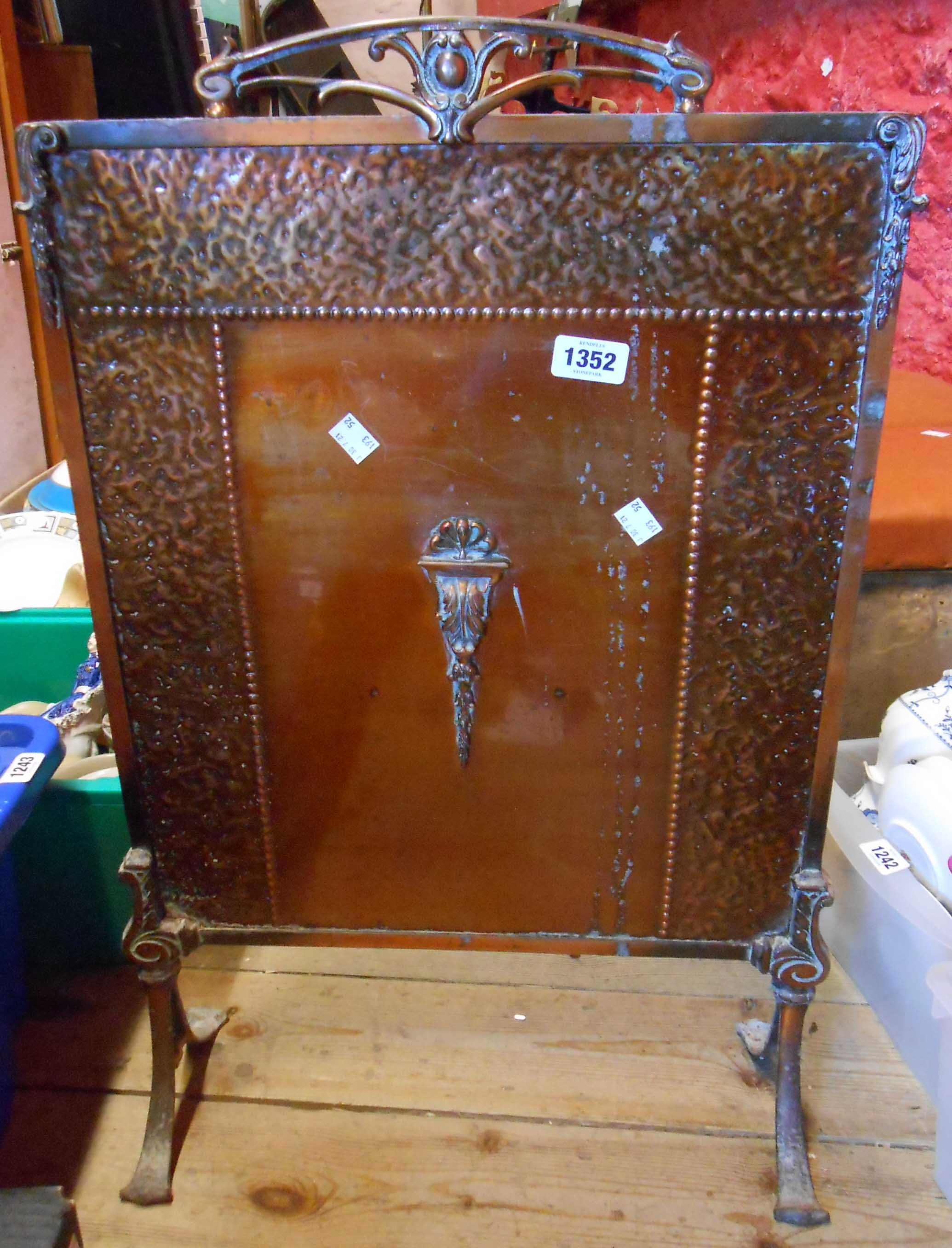A coppered brass and iron fire screen with beaten effect decorative border and Rococo style handle