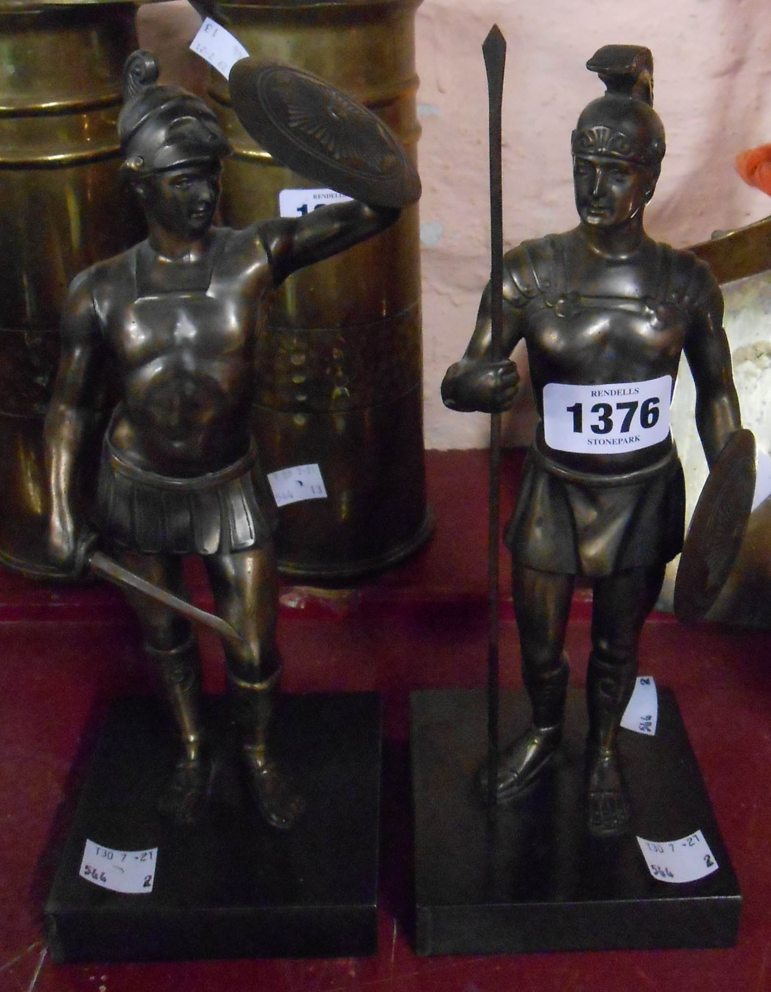A pair of cast metal statues depicting Roman soldiers with bronzed finish