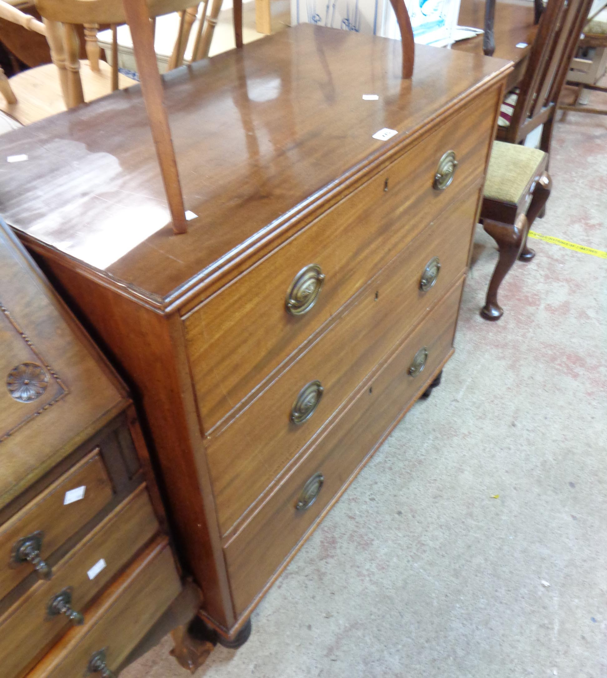 A 94cm 19th Century mahogany chest of three long graduated drawers, set on later turned legs - top