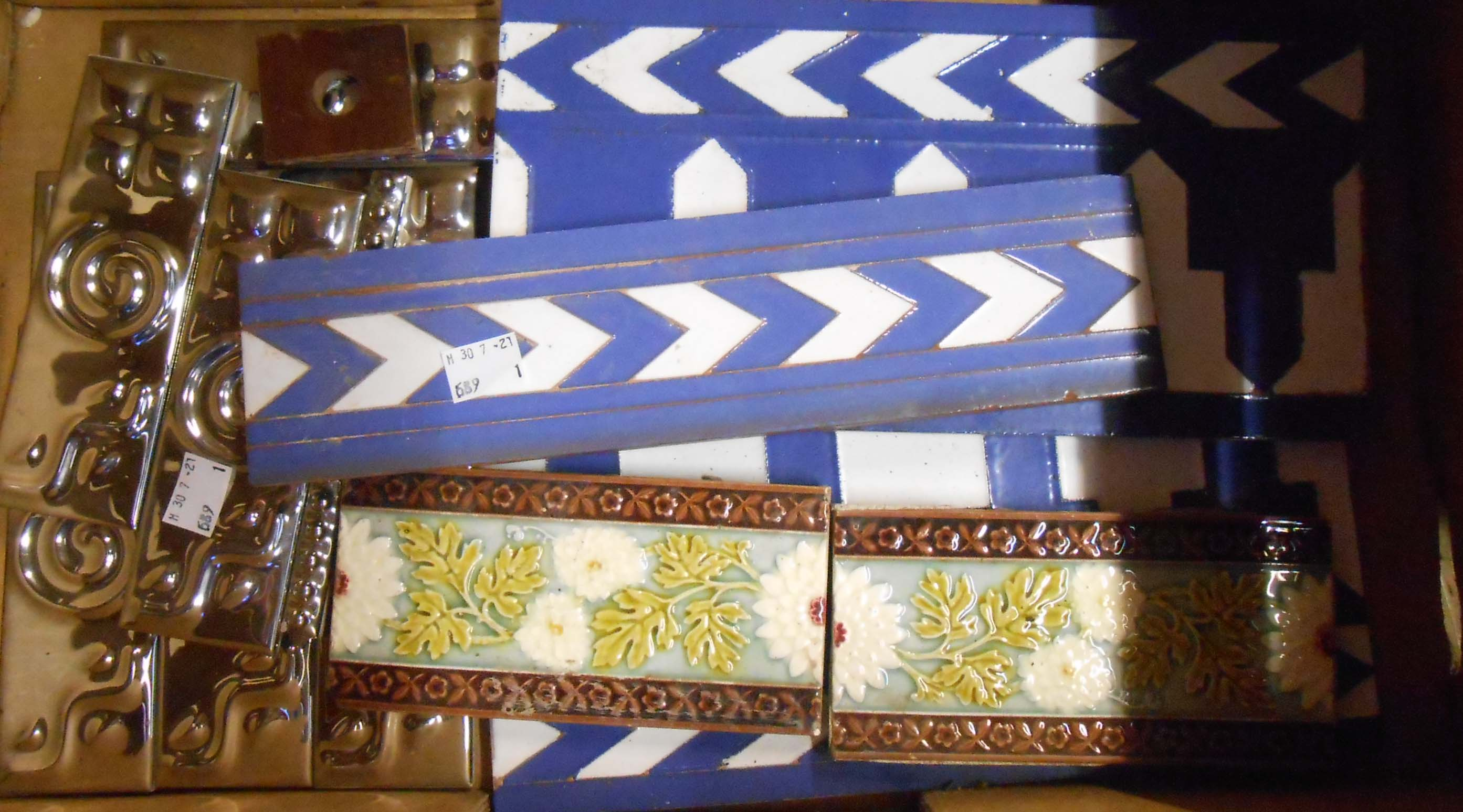 A box containing assorted ceramic fireplace surround tiles
