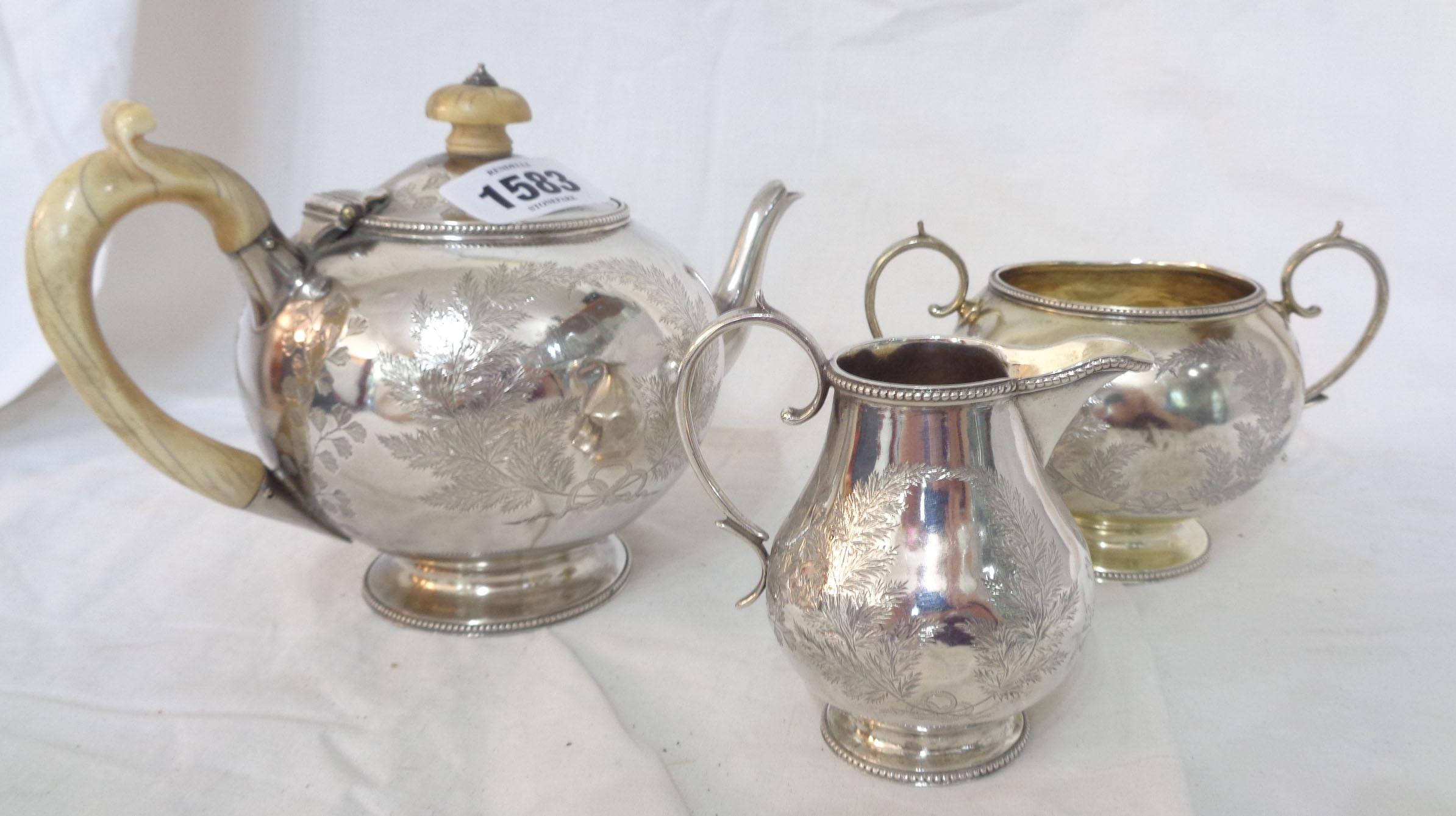 A Victorian silver three piece tea set of globular form with engraved fern decoration - London