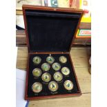 A cased set of twelve 22ct. gold plated medallions, each with central hand painted roundrels,