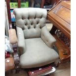 A late Victorian low armchair with button back green cotton upholstery, set on turned front legs and