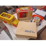 Four vintage Fisher Price toys including medical kit, pull along bus and music box TV