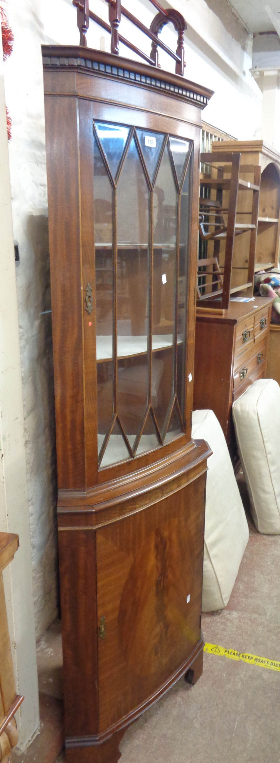 A 64cm reproduction mahogany bow front corner cabinet with glazed top and cupboard under, set on