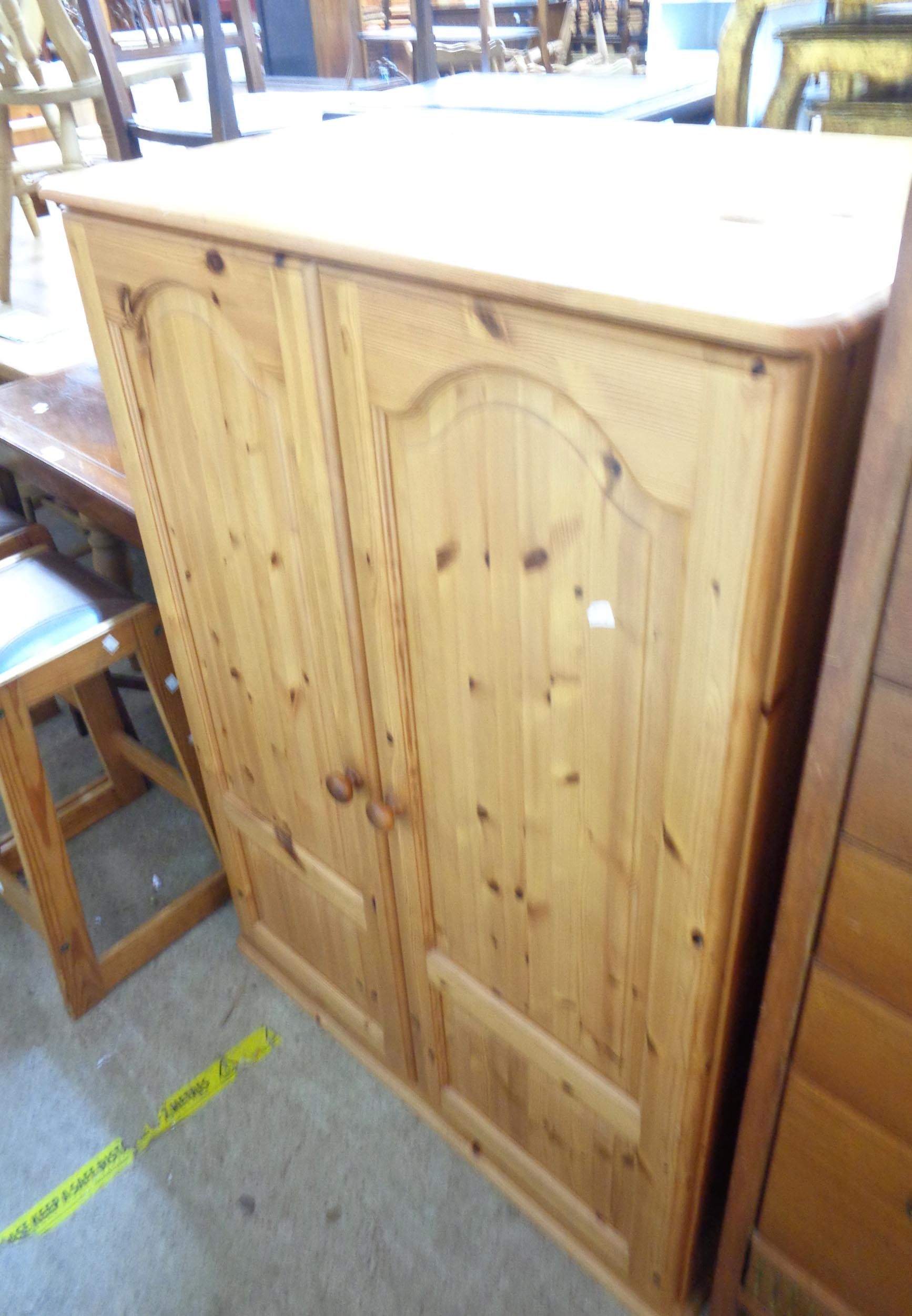 A 91cm modern polished pine wardrobe with hanging space enclosed by a pair of panelled doors