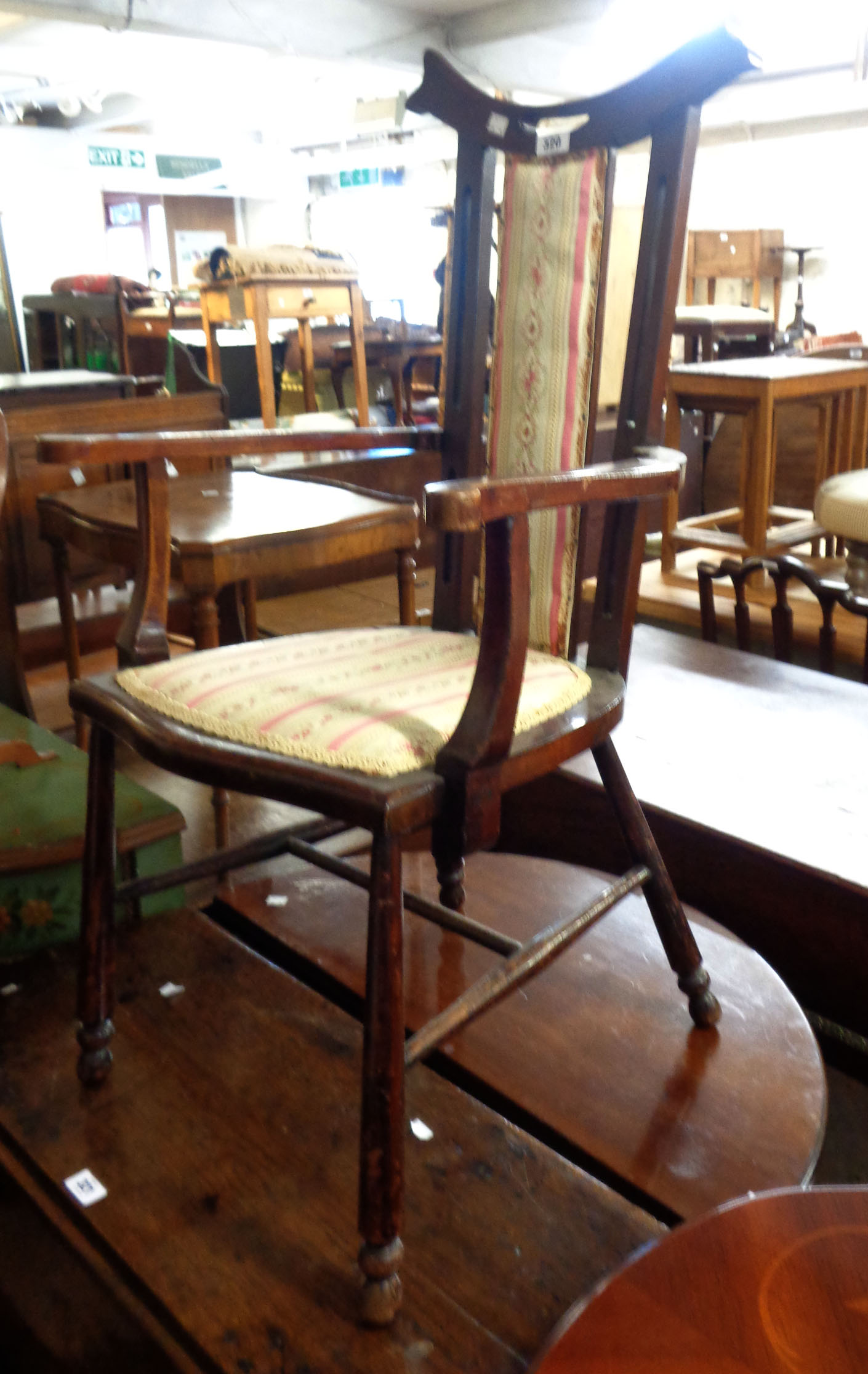 An early 20th Century stained walnut framed elbow chair with upholstered back and seat, set on