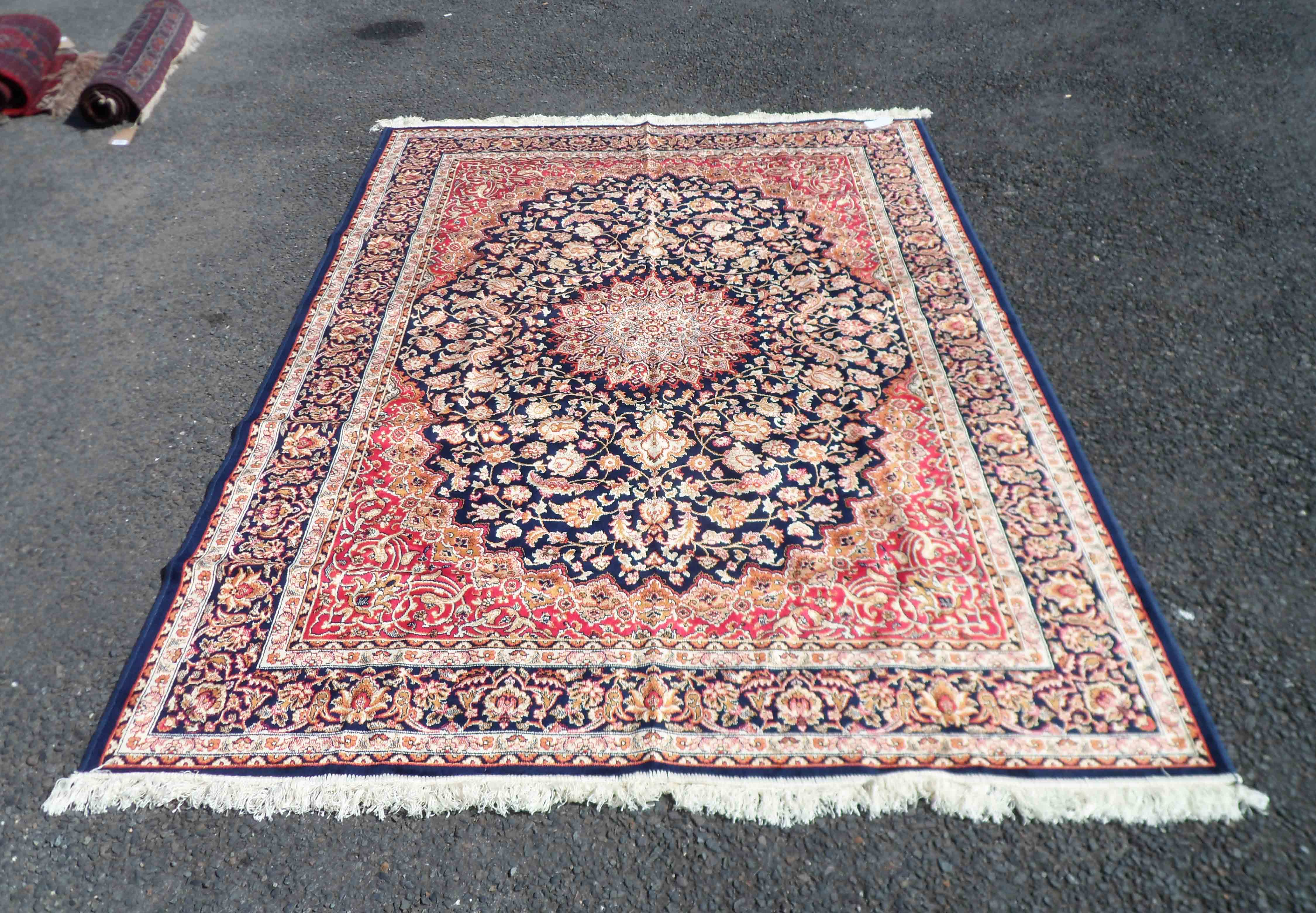 A late 20th Century blue machine made Kashan rug with central medallion and coloured floral
