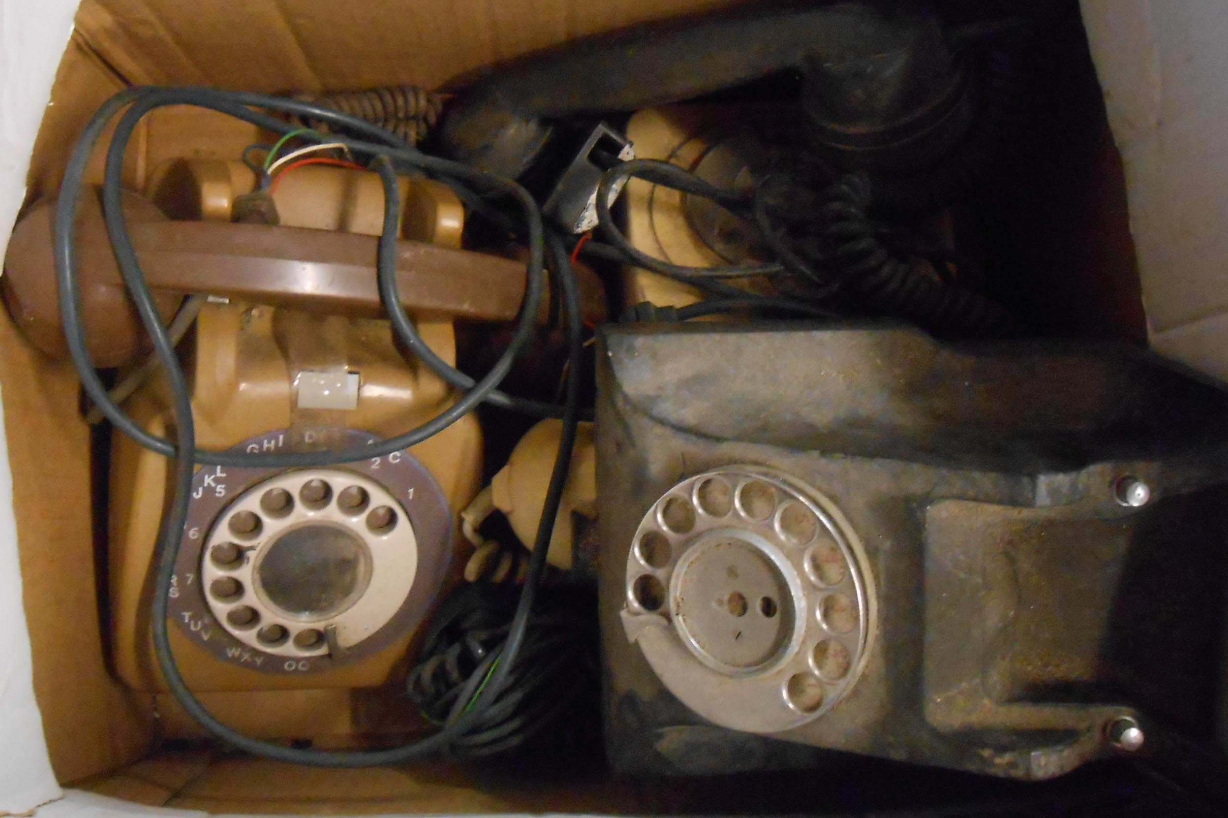 A box containing three vintage telephones