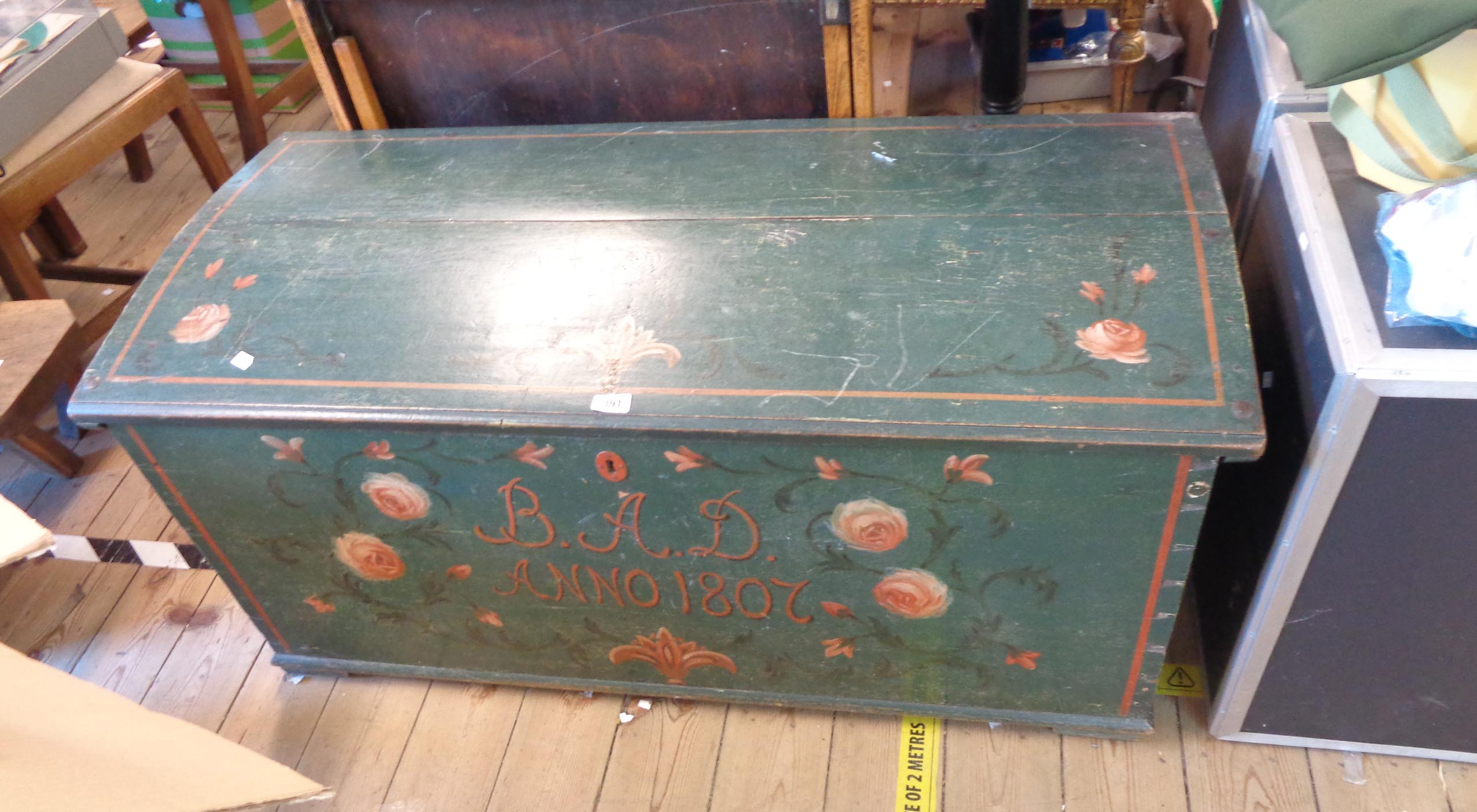 A 1.23m antique oak dome-top linen chest with painted floral decoration on green ground, text B.A.D.