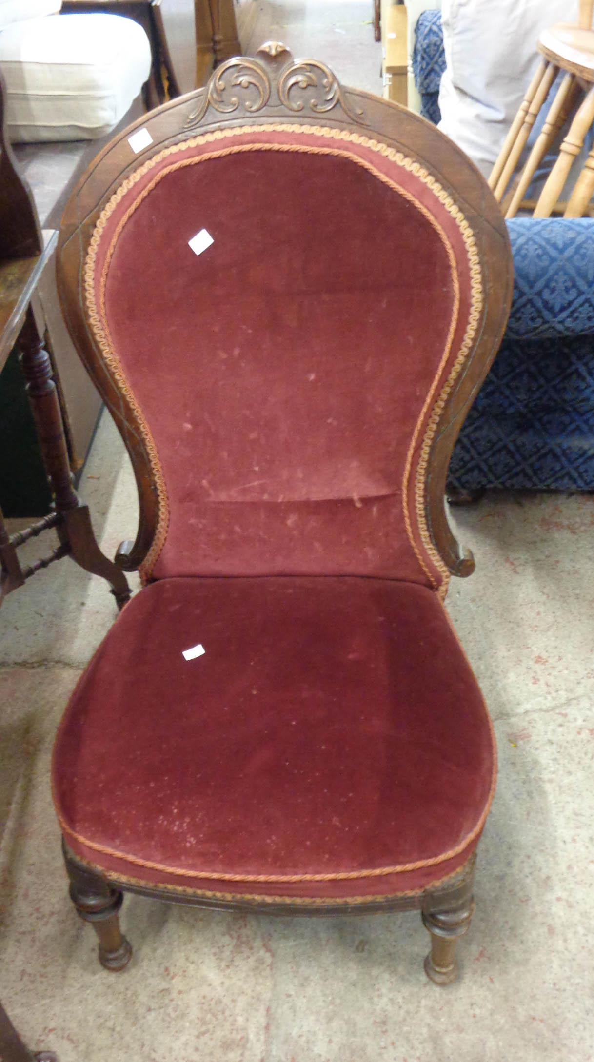 A Victorian walnut part show frame spoon back nursing chair with piped upholstery, set on turned