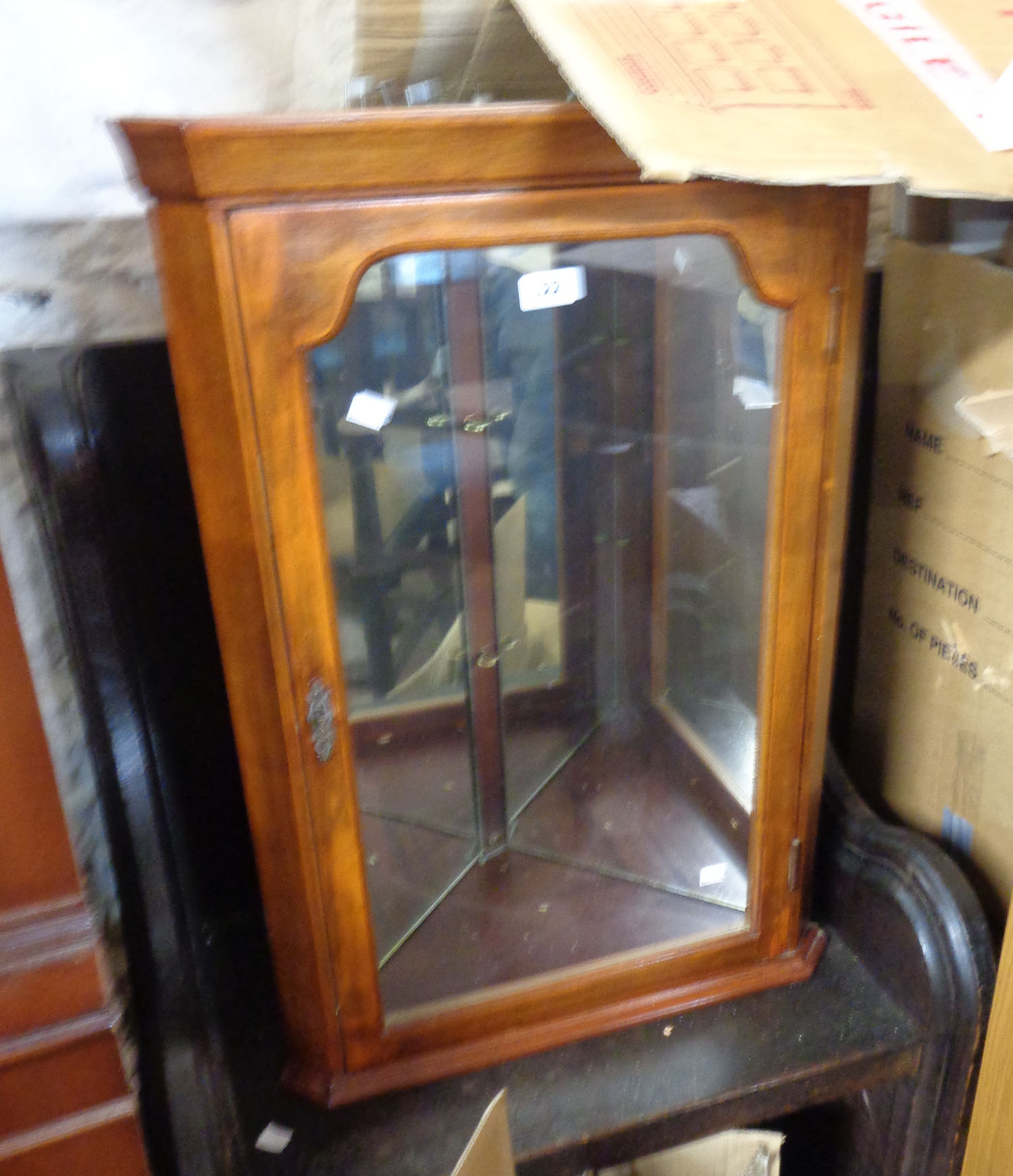 A small corner display cabinet with later light fittings