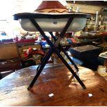 A vintage enamelled bidet, on folding metal stand