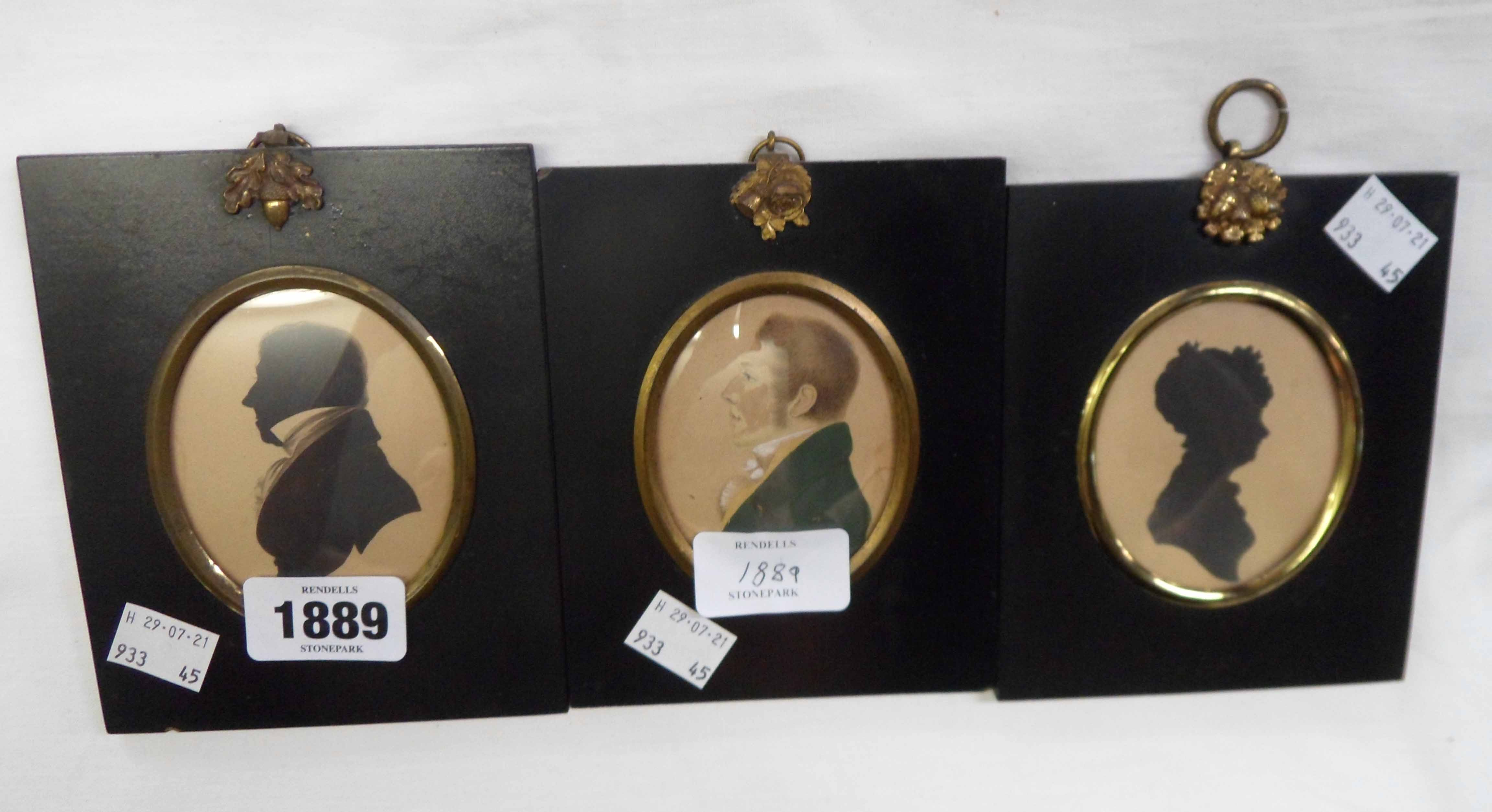 A pair of ebonised papier-mâché framed oval silhouette profile portraits of a lady and gentleman -