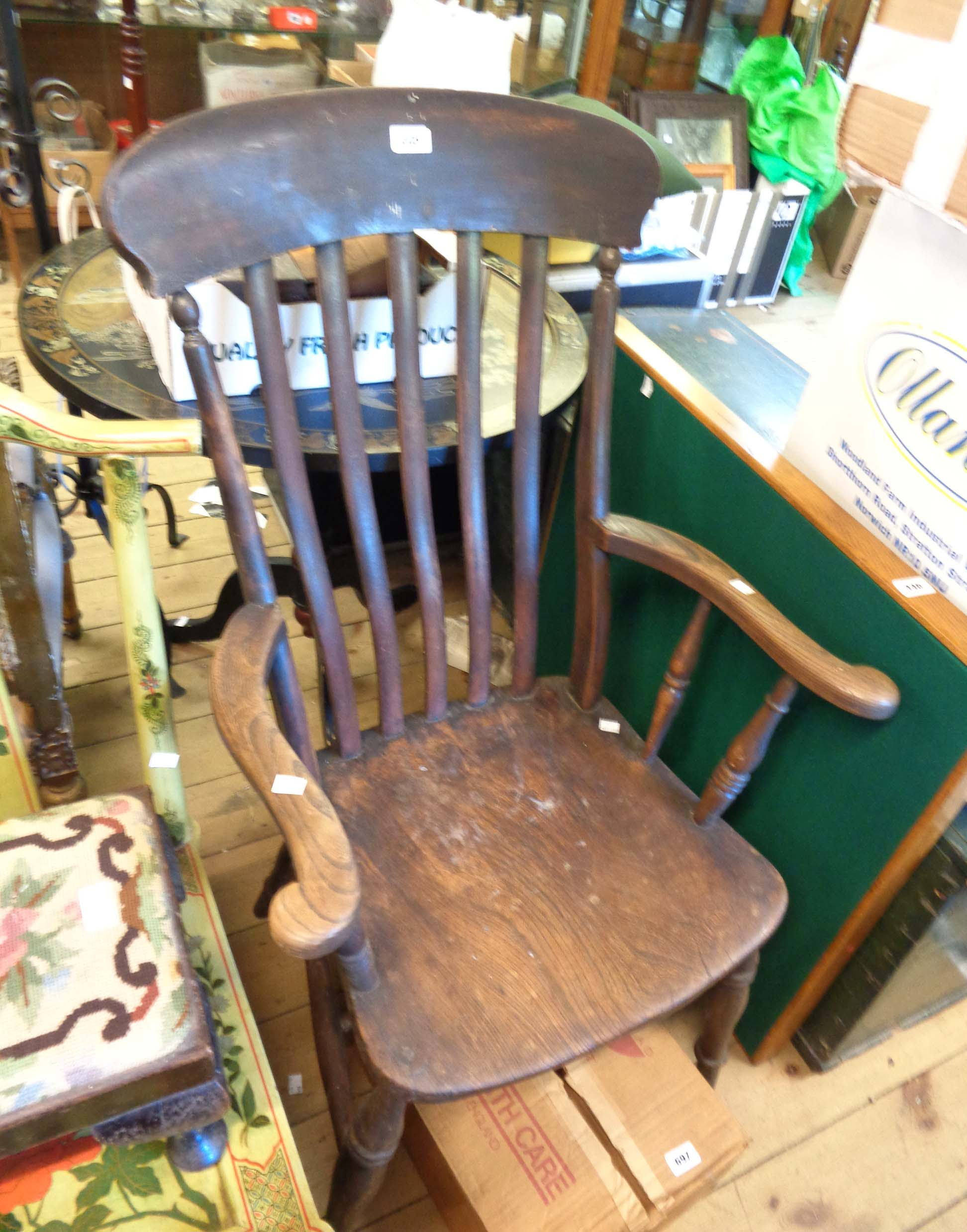 An antique elm high lathe back Windsor elbow chair with solid moulded seat, set on ring turned