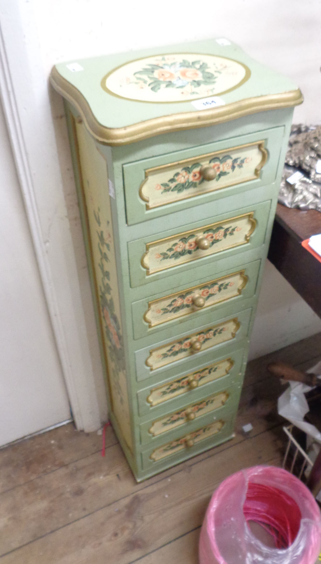 A 30cm wide modern decorative narrow chest with flight of seven drawers, with all round painted