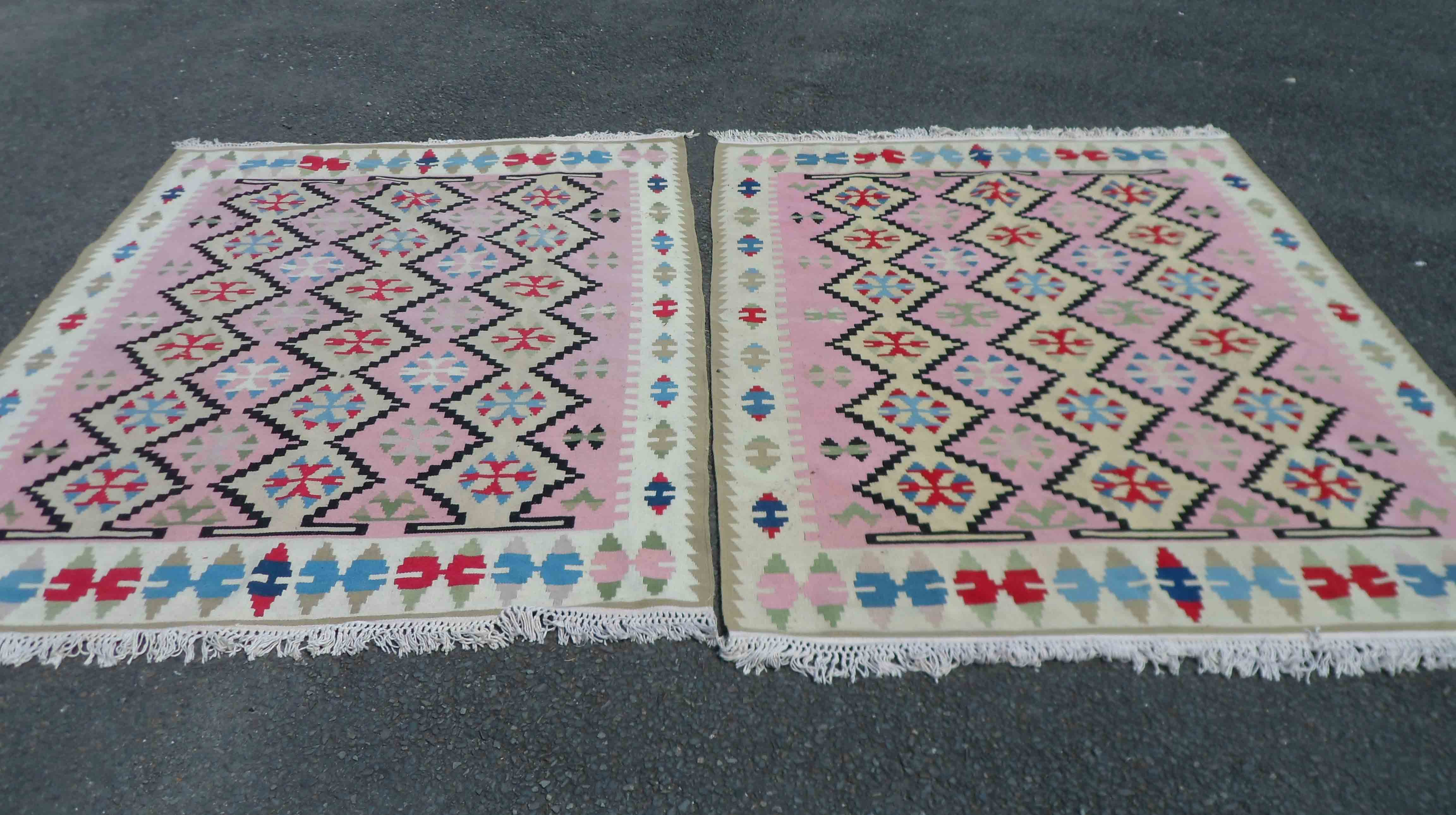 A pair of 20th Century handmade Pakistani kelims with polychrome geometric designs on a pink and