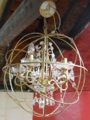 A modern hanging chandelier light fitting with glass sconces and drops, metal frame enclosed in