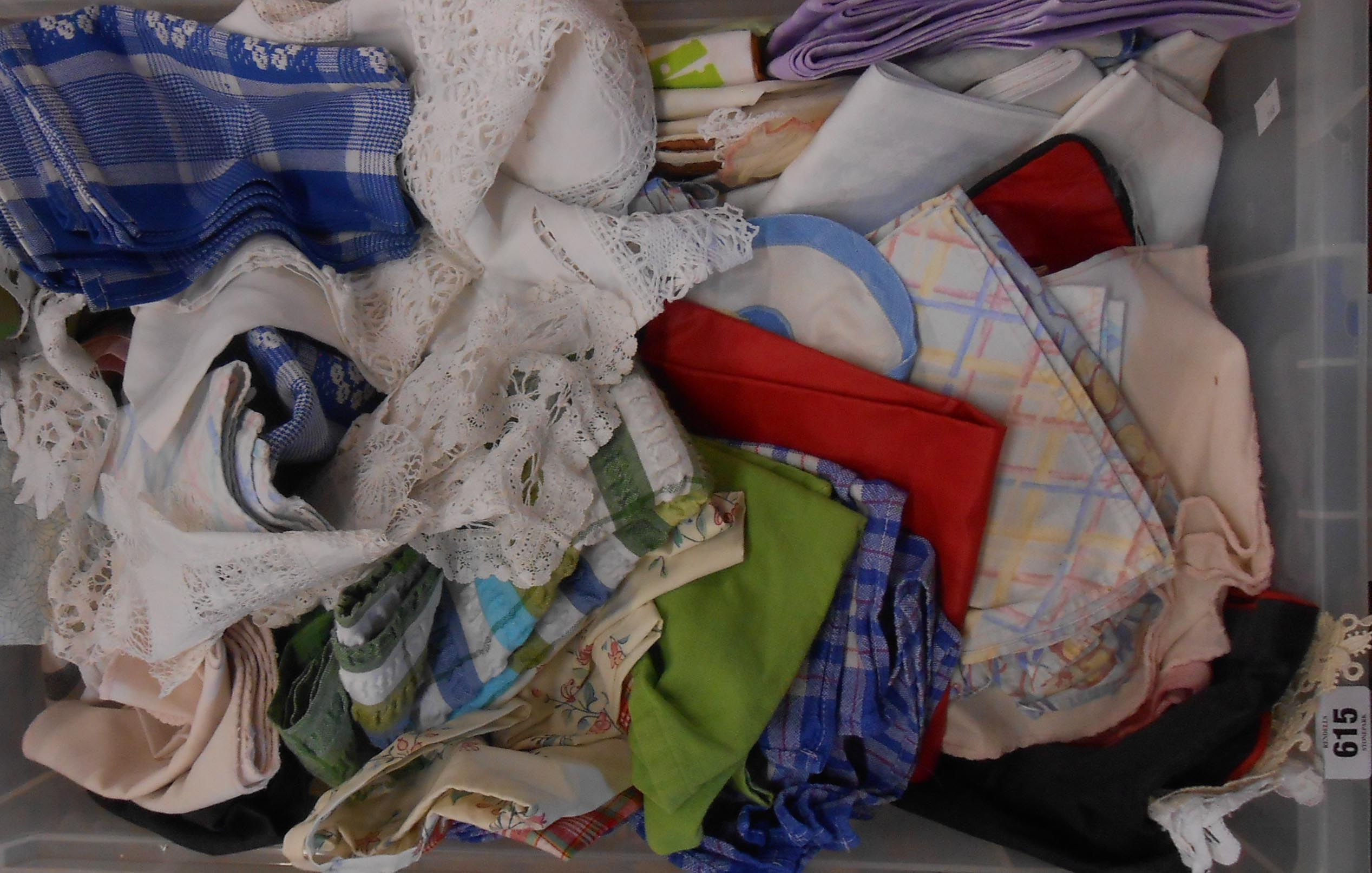 A crate containing assorted vintage textiles including tablecloths, table runners, tray cloths,