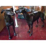 A pair of cast metal greyhound figurines with bronzed finish