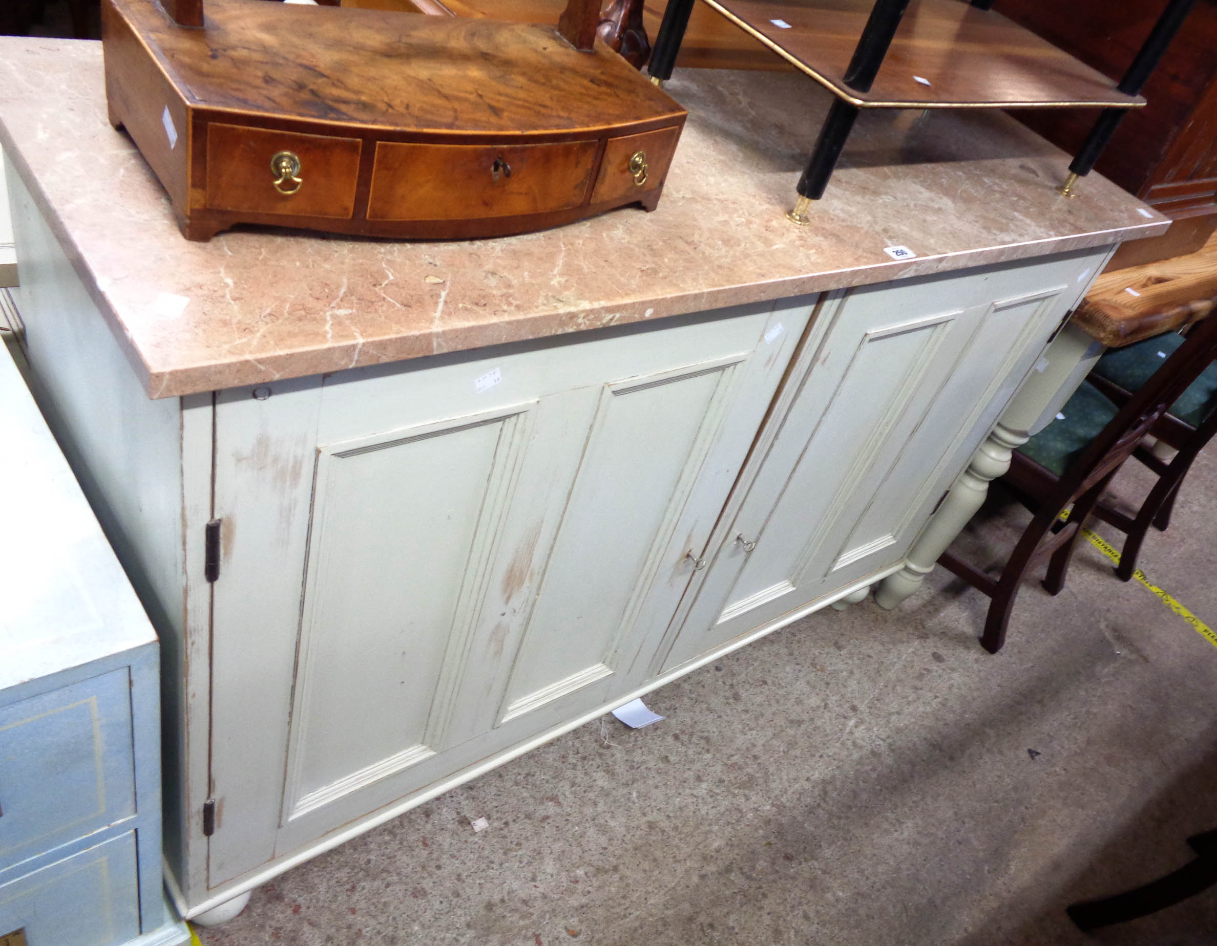A 1.4m marble topped painted pine side cabinet with shelves enclosed by a pair of panelled doors,