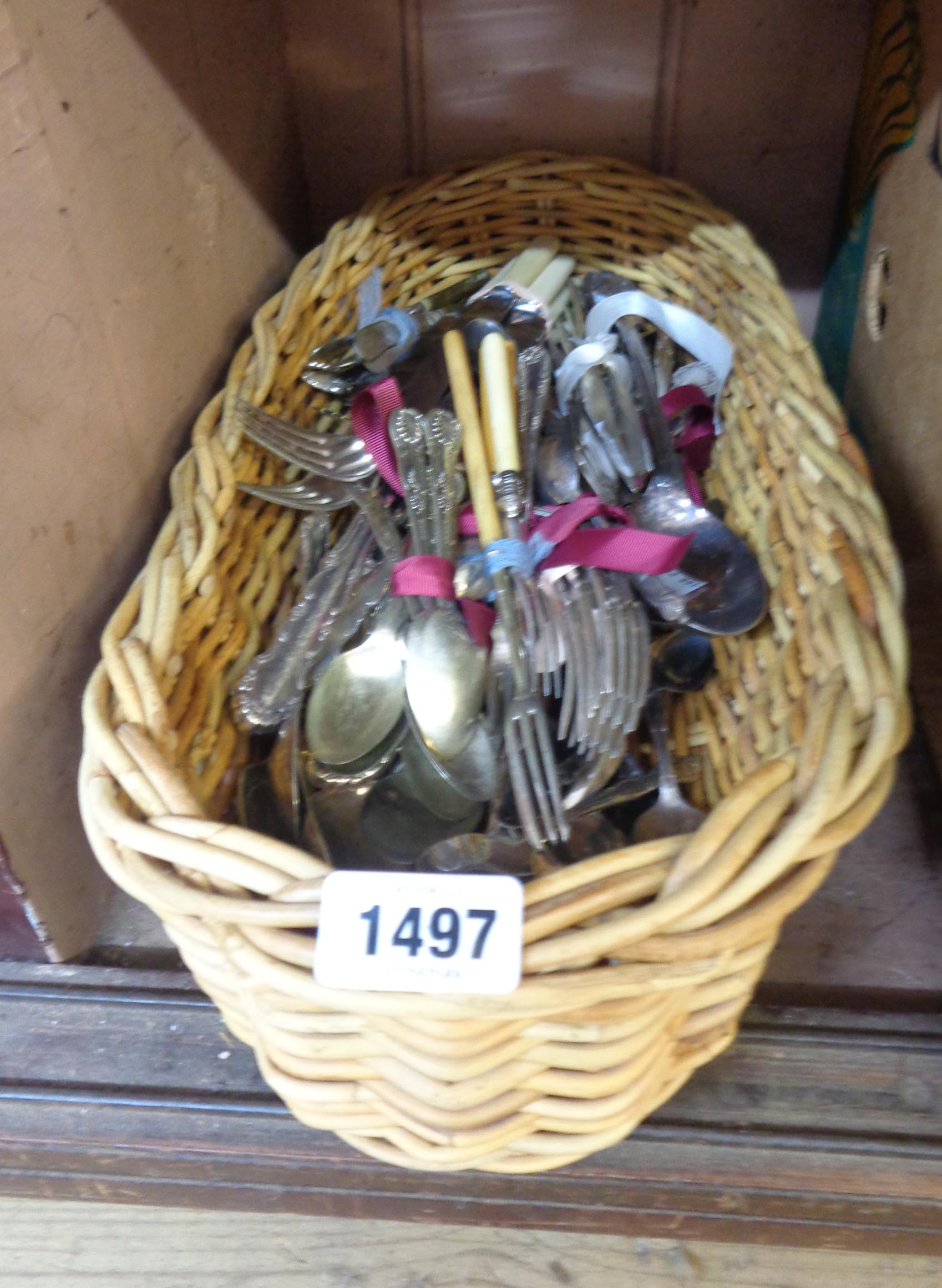 A wicker tray containing a quantity of assorted silver plated and other cutlery